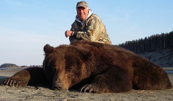 a hunter posses with his Brown Bear